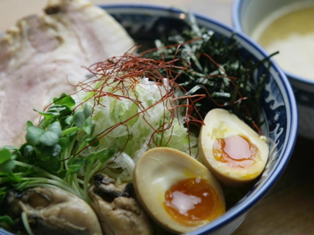 An image of oyster ramen form Saichi Ramen in Kinshicho, Tokyo. The ramen has a piece of chashu, oysters, an egg, copious amounts of green onion, vegetables, and seaweed.