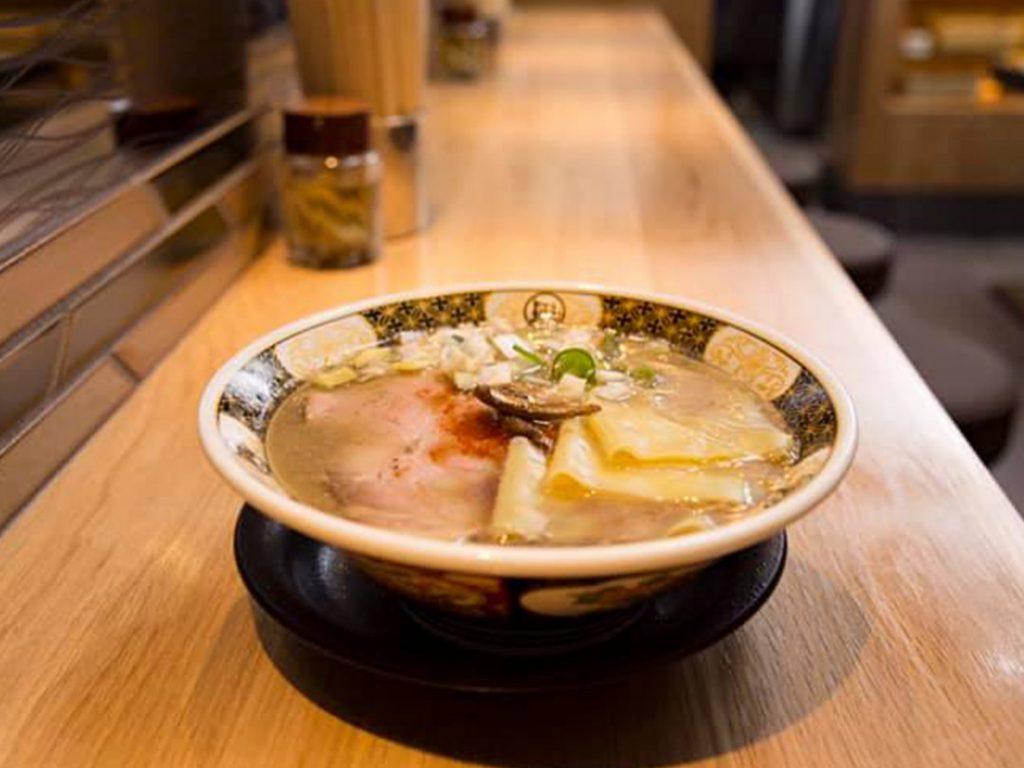 A bowl of ramen from Ramen Nagi, a ramen shop with locations all over Tokyo, they specialize in a fish base broth. The image includes a picture o the chashu meat and a flat noodle that Nagi uses for extra texture.